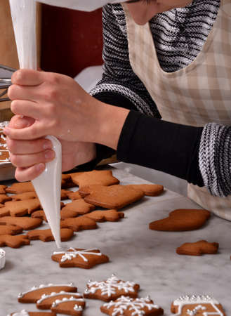 christmas baker's: Pastry chef woman preparing christmas cookies holding a vanilla cream cone.