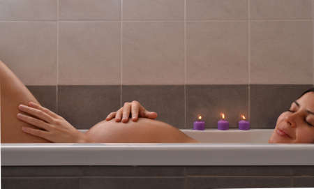 lying in bathtub: Serene pregnant woman in relaxing candle ambient at bathtub before give Birth. Beautiful young pregnant woman at beauty salon spa getting a body treatment.