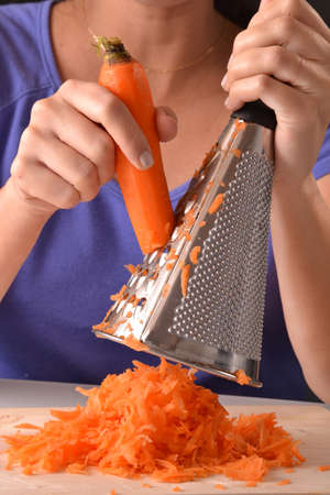 grating: Woman grating carrot.