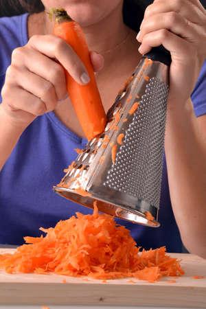 grating: Woman grating carrot.