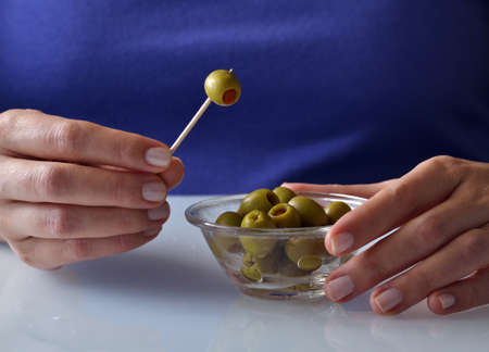 toothpick: Picking olives with toothpick Stock Photo
