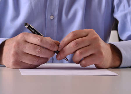 Man hands detail writing and signing a document Stock Photo