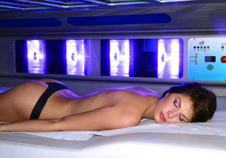 woman lying down: Beautiful woman lying down on solarium spa bed