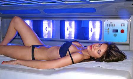 solarium: Beautiful woman lying down on solarium spa bed