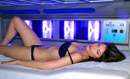 Sensual latin woman lying down on solarium spa bed at beauty center.