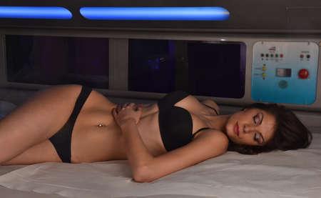 solarium: Sensual latin woman lying down on solarium spa bed at beauty center.
