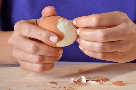 Woman shelling an egg