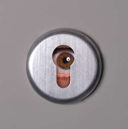 Person looking in keyhole Stock Photo