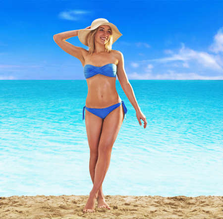 Summer blonde woman on the beach wearing hat