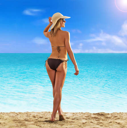 Summer blonde woman on the beach wearing hat.