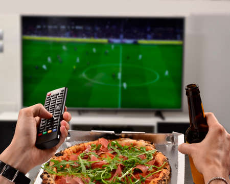 Man watching football game on television andean pizza Stock Photo