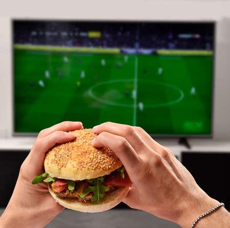Eating burger and watching football game