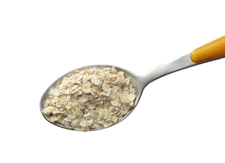 Dry oatmeal in spoon on white background. Stock Photo