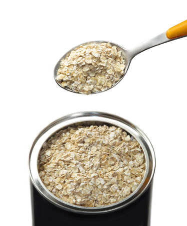 Dry oatmeal container and spoon on white background.