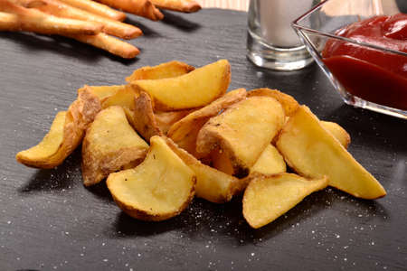 Slices of french fried potatoes and sauces.