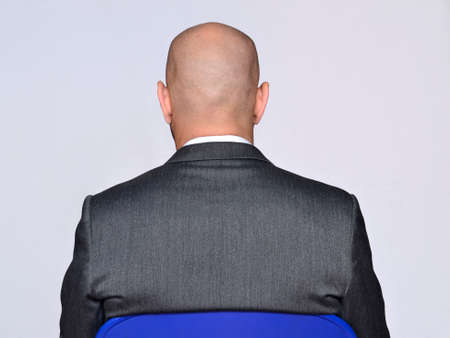 Back view from a bald head sitting on chair