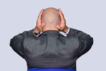 Worry businessman touching his head.