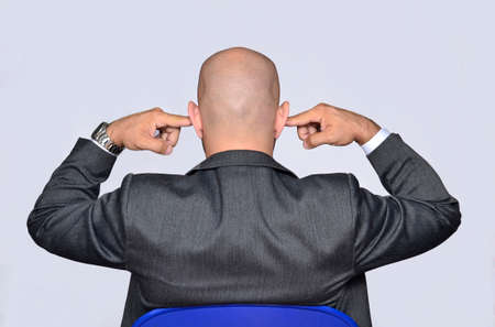 Back view from bald head businessman covering his ears.