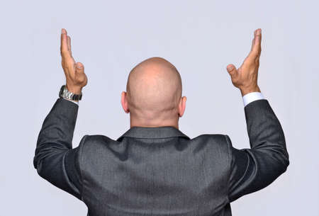 Businessman with raised hands, praying, desperate. Stock Photo