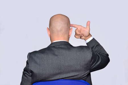 Businessman pointing hand gun on head