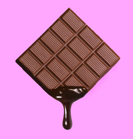 Dark chocolate bar and melted brewing drop on pink background. Stock Photo