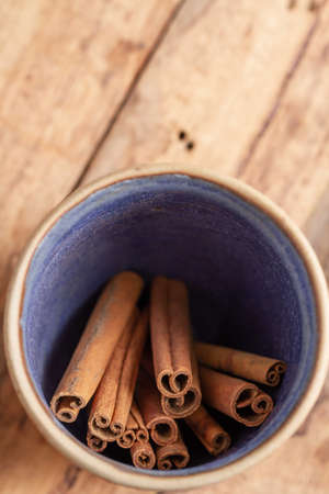 cinnamon sticks in a ceramic bowl on a wooden table