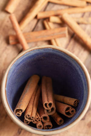 Cinnamon sticks in a bowl on wooden background