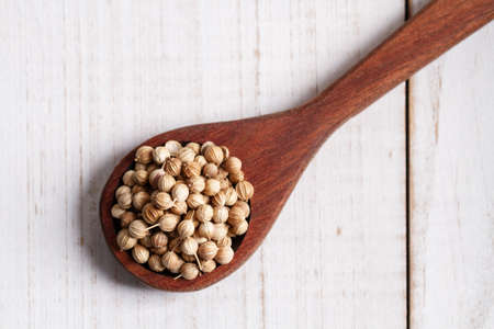 dried coriander on wooden spoon