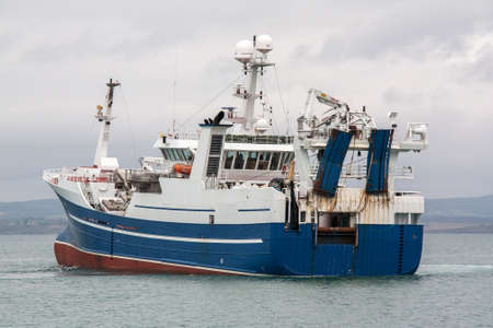 Departure professional fishing trawler in very overcast Stock Photo