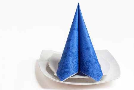 Blue paper napkin folding cone on white plate Stock Photo