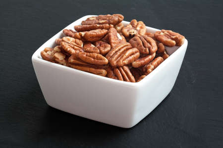 pecans: Pecans in a bowl on a black background