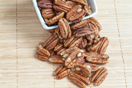 pecans: Pecans in a cup on bamboo Stock Photo