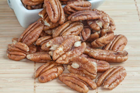 dietetics: Pecans in a cup on bamboo background