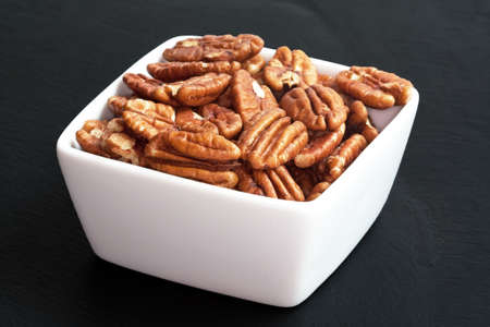dietetics: Pecans in a bowl on a black background