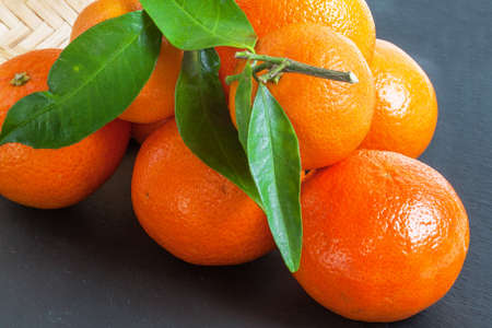 clementines: Clementines and leaves on slate background Stock Photo