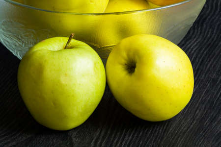 Golden apples to a bowl on a black background