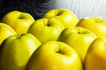 Golden apples lined up on a black background Stock Photo