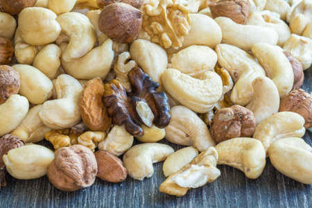 dietetics: cashews and walnuts in a pile on a dark background