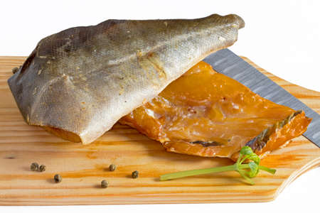 Different smoked fish on a cutting board on a white background
