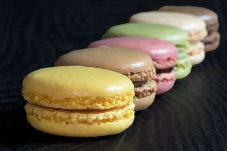 Macaroons of different colors in line on black background