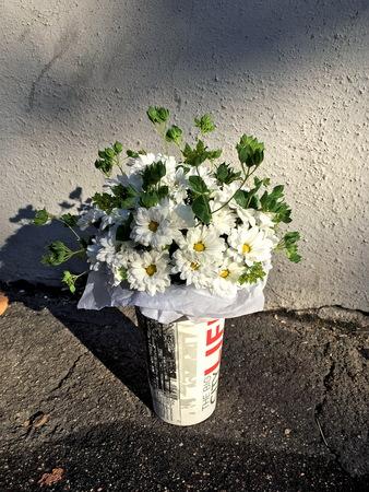 White flower in the vase on the street.