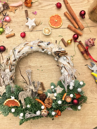 Christmas wreath on wooden table top view. Top down view of florist's worktable. Making of Christmas wreath. Getting ready for Christmas. Christmas tree decoration toys, gift box and scissors over rustic wood table background, top view