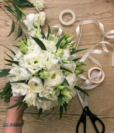 Classic white bridal bouquet. Wedding bouquet made of of white Ranunnculus and white eustoma on a wooden background. Florist workplace.
