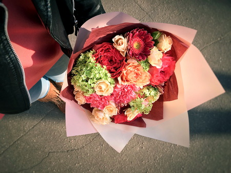 A beautiful bouquet of flowers with beigerose, pink dianthus, gerbera, spray roses, in the hands of a girl.