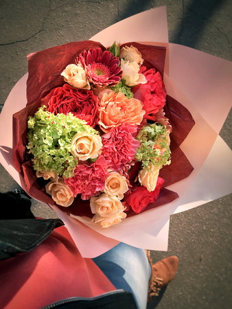 A beautiful bouquet of flowers with beigerose, pink dianthus, gerbera, spray roses, in the hands of a girl. Reklamní fotografie - 122629762