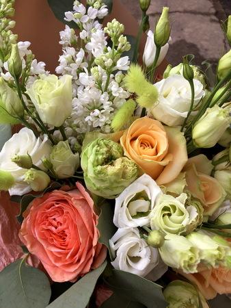 Close-up Beautiful Bouquet. Bouquet of flowers white lilac, white Eustoma, orange rose. Beautiful bright flowers background. Beige bouquet 版權商用圖片