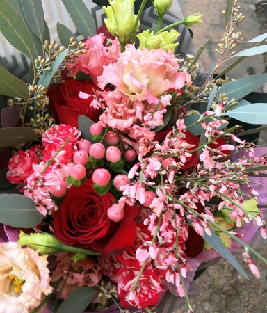Close-up Beautiful Bouquet. Bouquet of flowers pink genista, pink Eustoma, red rose, pink hypericum berries , spray roses. Beautiful bright flowers background.
