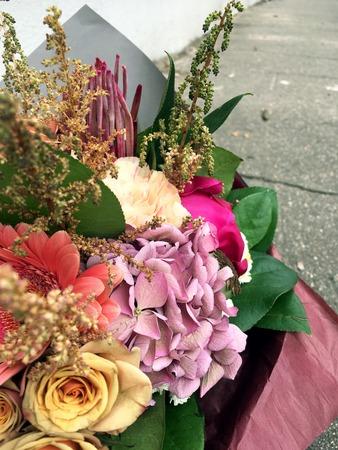 Close-up Beautiful Bouquet. Bouquet of flowers pink hydrangea, orange roseand green leaf. Beautiful bright flowers background. beige bouquet 版權商用圖片