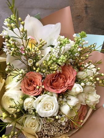 Close-up Beautiful Bouquet. Bouquet of flowers white orchid Cymbidium , white Eustoma, white spray rose, white hamelacum. Beautiful bright flowers background. Beige bouquet 版權商用圖片