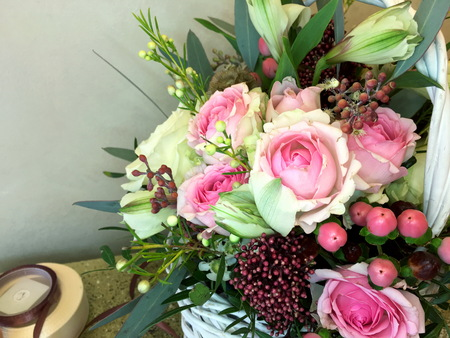 Close up of bouquet of fresh flowers on a light background. Pink and yellow roses, green buds, pink roses, hypericum berries and greens in a bouquet of fresh flowers on a light background. 版權商用圖片